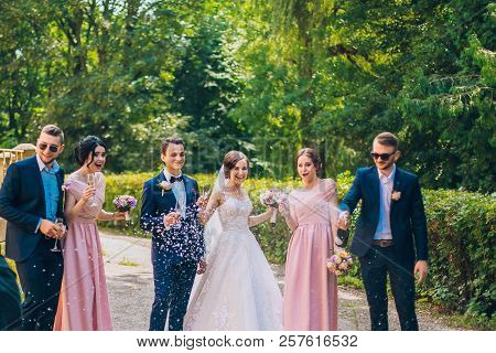 Bride And Groom With Happy Groomsmen And Bridesmaids Having Fun And Popping Champagne, Newlyweds Wed