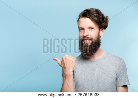 Smiling Young Man Pointing Sideways With Thumb As If Showing Smth. Portrait Of A Bearded Guy On Blue