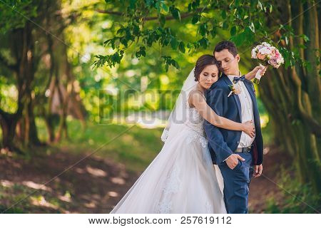 Romantic Wedding Moment, Couple Of Newlyweds Smiling Portrait, Bride And Groom Hug While On A Walk I
