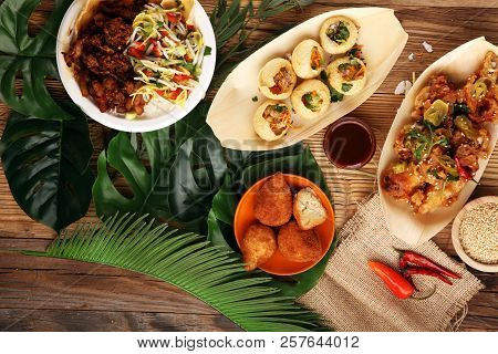 Various Street Food With Pani Puri, Chicken Wings And Coxinha On Rustic Background. Balinese Nasi Ca