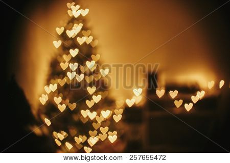 Christmas Abstract Background, Beautiful Christmas Tree Golden Lights Hearts Bokeh. Blur Of Yellow G