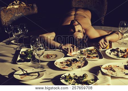 Handsome man or sexy muscular macho athlete bodybuilder with muscle torso undressed to waist lying on table with leftovers or residues food on dirty plates after banquet in restaurant. poster