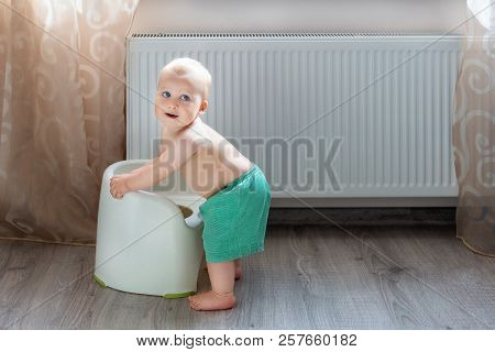 Cute Little Blond Caucasian Boy In Funny Green Shorts Playing With White Potty Indoor. Adorable Chil