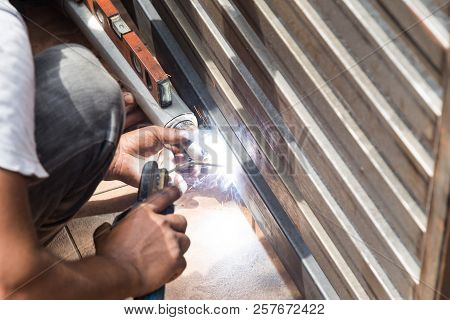 Closeup Of Worker Welding Auto Gate Arm Onto Metal Gate