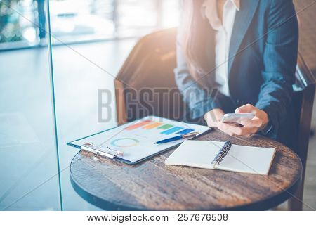 Business Woman Hand Are Using Cell Phones And Work On Charts And Graphs That Show Results In Office.