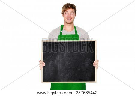 Small business owner showing blackboard board blank empty sign wearing green apron. Handsome young shop owner man isolated on white background smiling happy.