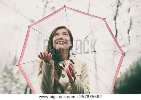 Autumn woman walking in rain with umbrella. Asian model looking up at rainy fall day with hand out and raincoat outside in nature forest. Multiracial Asian girl.