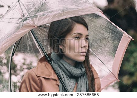 Autumn rainy grey day sad girl pensive. Asian woman in depression during fall season mood change.