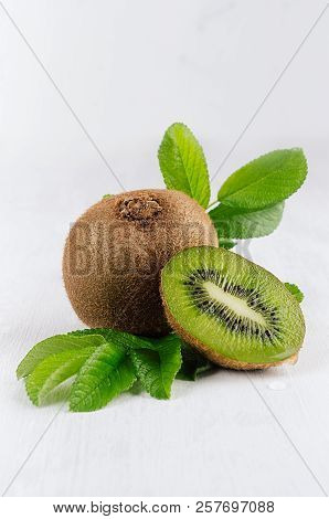 Ripe Kiwi With Juicy Slice And Drop Juice, Green Young Leaves On White Soft  Wood Board, Vertical. F