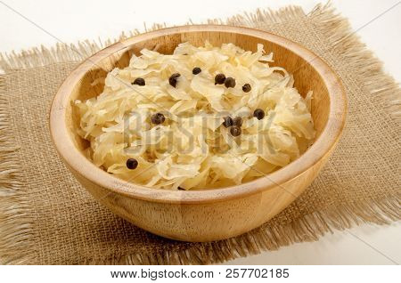 Home Made Sauerkraut In A Wooden Bowl With Juniper Berries On Jute