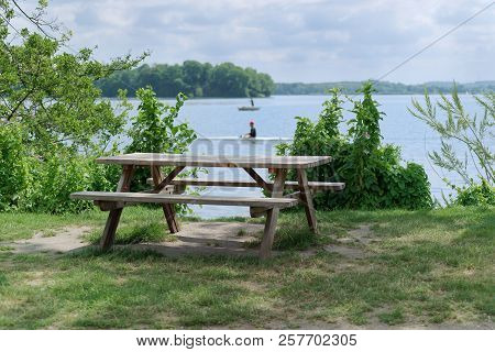 Picnic Place At The Lake Coast - Tranquil Scene Of Wooden Table With Two Benches At The Lake Coast