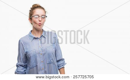 Young blonde business woman making fish face with lips, crazy and comical gesture. Funny expression.