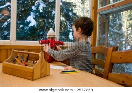 Boy Drawing A Picture And Playing With Doll