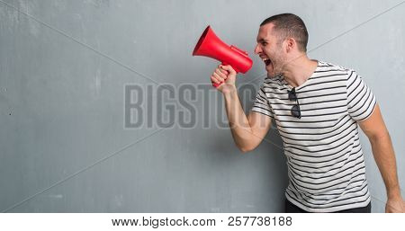 Young caucasian man over grey grunge wall shouting trough megaphone annoyed and frustrated shouting with anger, crazy and yelling with raised hand, anger concept
