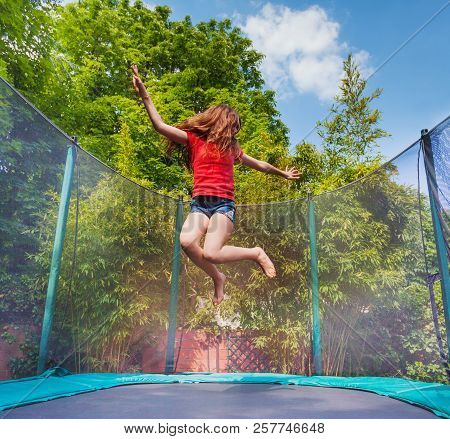 Active Girl Jumping High On Trampoline Outdoors