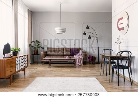 Real Photo Of Light Grey Living Room Interior With Window With Curtains, Leather Couch, Table With T