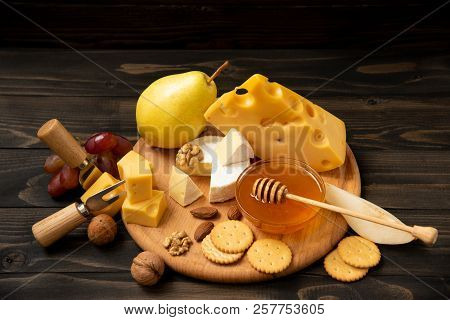 Assorted Cheeses On A Round Wooden Board