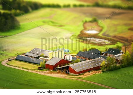 Rural Farm In Red Colors With Green Fields Around In The Agriculture Industry Seen From Above