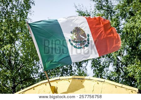 Mexican Flag On A Yellow Building Waving In The Wind In Mexico
