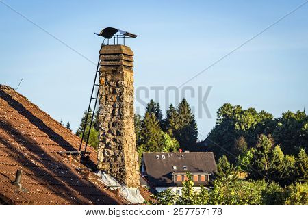Old Chimney With A Ladder On A Roof In The Morning Sun