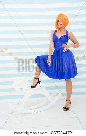 Tame anyone she wants. Comic and humorous concept. Woman playful but confident mood having fun. Never too late to tame horse. Girls power in beauty. Lady red ginger wig blue dress and rocking horse. poster