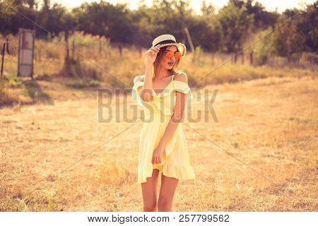 Beautiful Young Woman In Yellow Summer Dress, Rounded Sunglasses And Straw Hat Having Fun Outdoor In