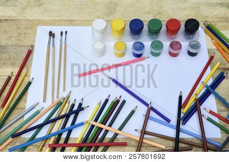 Art Concept. Many Colored Pencils, Brushes And Jars Of Paint On A Blank Sheet Of Paper. Wooden Table