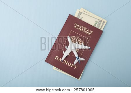 Airplane On The Cover Of A Russian Passport. Dollars. Travel Concept. Blue Background
