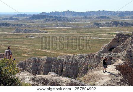 Badlands National Park In South Dakota - September 1, 2018: Two Unidentified Tourist Enjoying The Vi