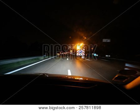 Shot From Inside Of Car Driving Down Road In Night Time With Blurry Lights Of Road Signs And Securit