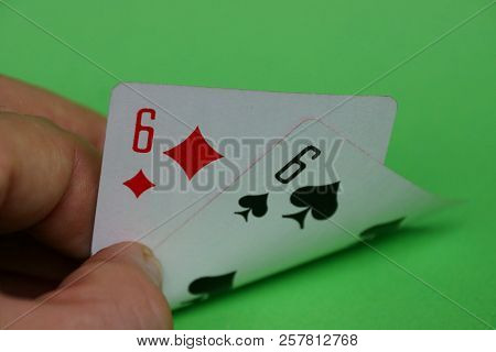Two Playing Cards With A Pair Of Sixes In Fingers Of Hands On A Green Table