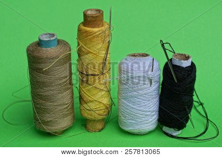 A Row Of Bobbins With Colored Threads And Needles On A Green Table