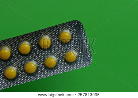 Gray Blister With Round Yellow Pills On A Green Background