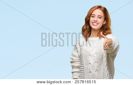 Young beautiful woman over isolated background wearing winter sweater smiling friendly offering handshake as greeting and welcoming. Successful business.