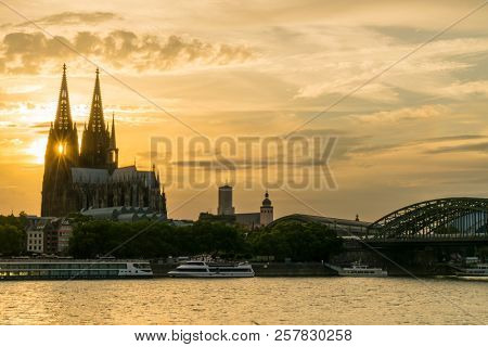 Sunset behind the twin gothic spires of Cologne Cathedral along side the Hohenzollern Bridge and river cruise boats on the River Rhine, Germany, Europe