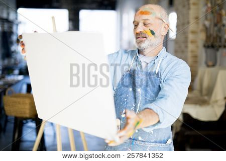 Aged artist with painted face standing in front of his easel and painting in studio of arts