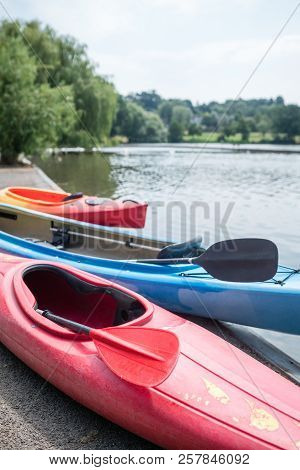 Three Kayaks On The Shore Of A Small Lake In Summer In Wimbledon Park In London