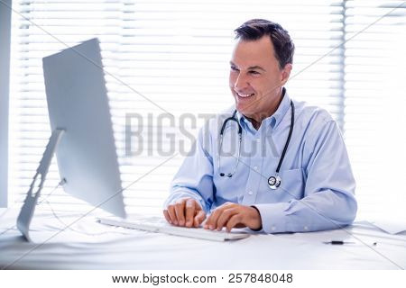 Male doctor working on personal computer in clinic