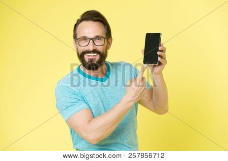 Man Excited About New Mobile Opportunities. Guy Eyeglasses Cheerful Pointing At Smartphone. Man Happ