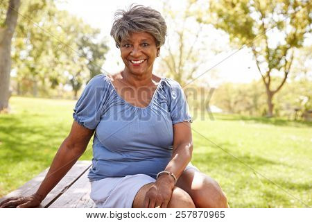 Outdoor Head And Shoulders Portrait Of Senior Woman Sitting In Park