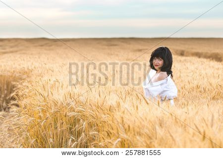 Cute Happy Beautiful Sexy Female Against A Background Of Wheat Field At The Time Of The Sunset. Shal