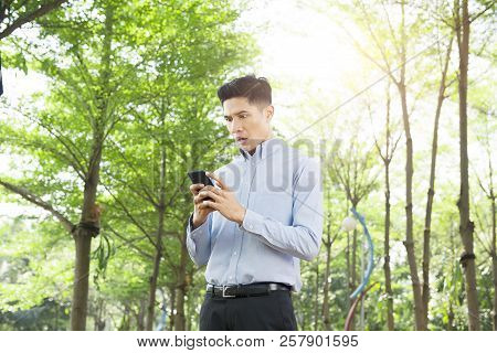 Shocked Asian Businessman After Read The Message On His Phone At Outdoor