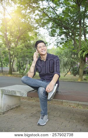 Young Asian Man Talking On Mobile Phone While Sitting On The Bench Park