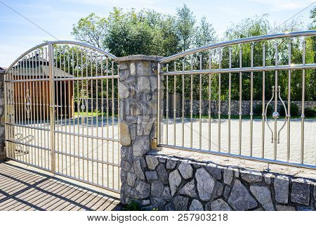 Fence Chrome Stainless Steel On Stone Wall. Chromium Fence With Gate