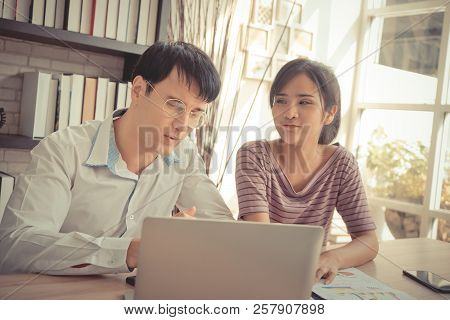 Business Couple Is Working Together On Laptop In Cafe