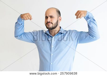Friendly Businessman Demonstrating Strength. Bearded Caucasian Man In Formal Shirt Grimacing And Fle