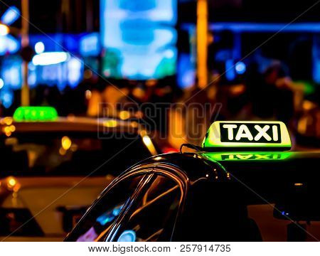 Taxi In The City At The Dark. Car With Glowing Taxi Sign Moving In The Night