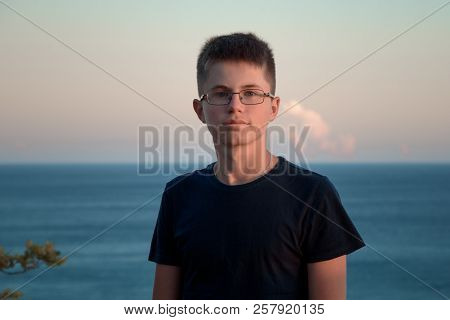 The Horizontal Portrait Of Cheerful Teenager Boy In Glasses Against The Sea At Sunset.