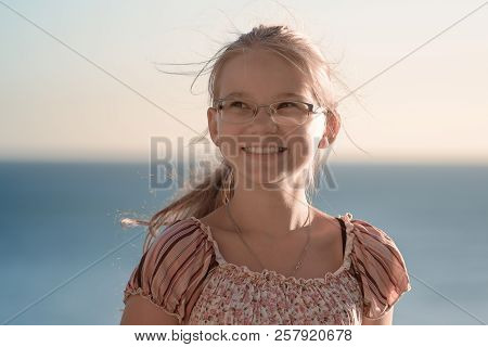 The Horizontal Portrait Of Cute Teenager Girl In Glasses Looking Away And Laughsing Against The Sea.
