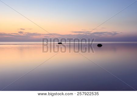 The Sky Is Reflected In The Sea At Sunset On A Long Exposure.